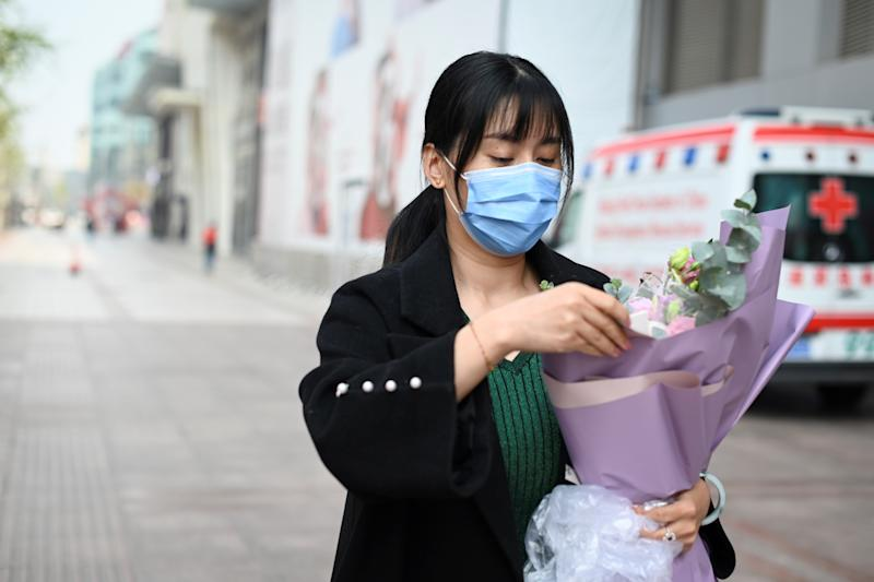 A woman wearing a face mask, amid concerns of the COVID-19 coronavirus, looks carries a bunch of flower as she walks along a road in Beijing on March 31, 2020. (Photo by WANG ZHAO / AFP) (Photo by WANG ZHAO/AFP via Getty Images)