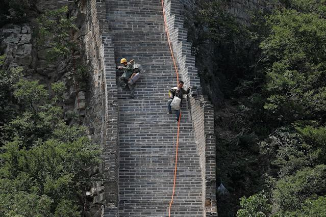 <p>Workers carry their tools and belongings as they climb down the Jiankou section of the Great Wall, located in Huairou District, north of Beijing, China, June 7, 2017. (Photo: Damir Sagolj/Reuters) </p>