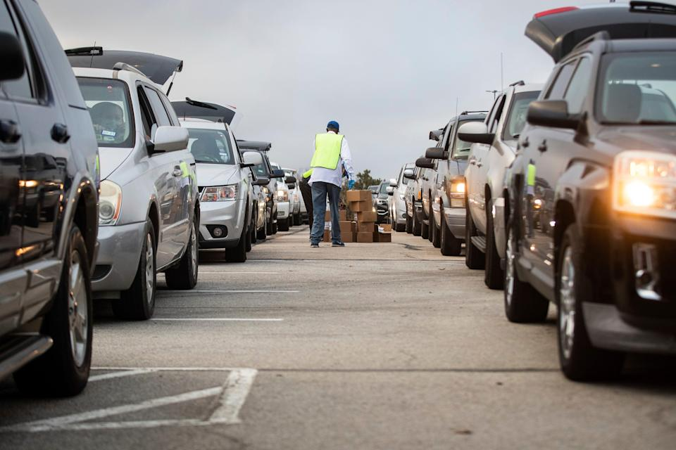 People line up in their cars to receive Thanksgiving meal boxes that include turkey and pantry items during the largest food giveaway of the Tarrant Area Food Bank amid the coronavirus pandemic Friday, Nov. 20, at AT&T Stadium parking lot in Arlington, Texas.