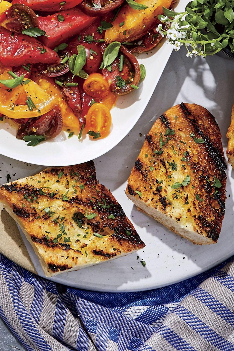 """<p>Homemade <a href=""""https://www.southernliving.com/recipes/garlic-bread-recipe"""" rel=""""nofollow noopener"""" target=""""_blank"""" data-ylk=""""slk:garlic bread"""" class=""""link rapid-noclick-resp"""">garlic bread</a> is a welcome addition to almost any meal, especially when it has a smoky <a href=""""https://www.southernliving.com/food/holidays-occasions/grilling-recipes"""" rel=""""nofollow noopener"""" target=""""_blank"""" data-ylk=""""slk:char from the grill"""" class=""""link rapid-noclick-resp"""">char from the grill</a>. Garlic butter makes the bread extra rich, but you can substitute olive oil if you wish. Sprinkle the cut bread with grated parmesan cheese just before serving if your crowd prefers cheesy garlic bread.</p>"""