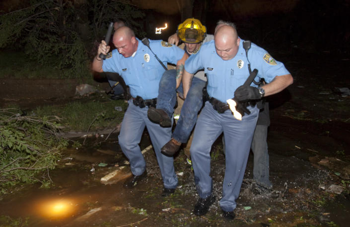 """Sheriff's deputies carry out an injured man from a south Wichita neighborhood after a tornado caused massive destruction in Wichita, Kan., late Saturday, April 14, 2012. Tornadoes were spotted across the Midwest and Plains on Saturday as an outbreak of unusually strong weather seized the region, and forecasters sternly warned that """"life-threatening"""" weather could intensify overnight. (AP Photo/The Wichita Eagle, Travis Heying) MAGS OUT; TV OUT"""