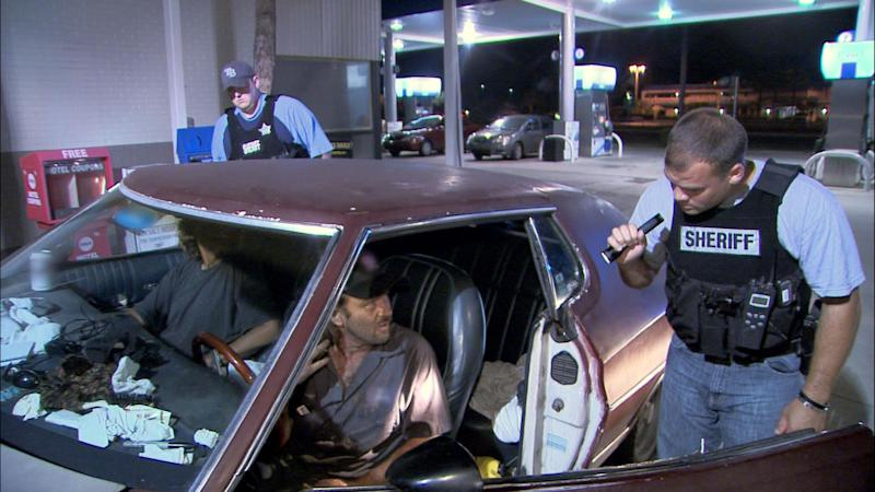 """This TV publicity image released by Fox shows police officers in Hillsborough, Fla., interrogating two occupants of a car for suspicious drug activity in an episode of """"COPS."""" The Saturday night television fixture """"Cops"""" is leaving Fox after 25 years to move to the Spike network. (AP Photo/Fox)"""