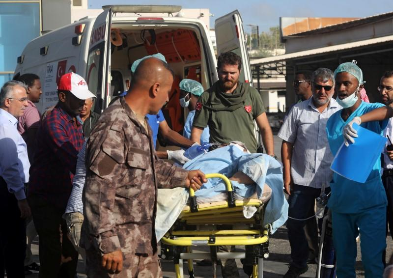 Paramedics assist a Turkish worker injured in an explosion in Afgoye town, before he boards a Turkish military cargo plane at the Aden Abdulle International Airport in Mogadishu