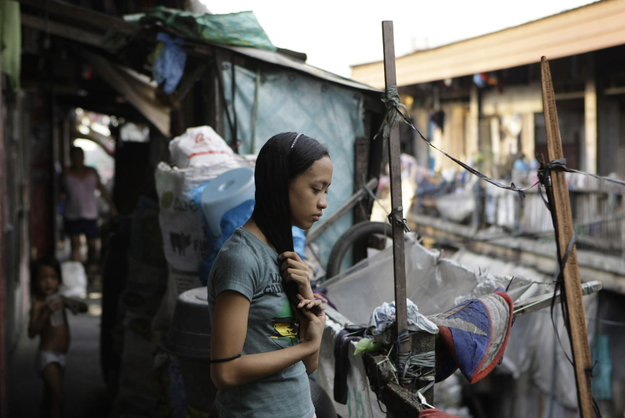 In this photo taken Dec. 4, 2012, Filipino slum dweller Jessa Balote holds her hair outside her cramped home at a place called Aroma in Tondo, Manila, Philippines. Balote, who used to tag along with her family as they collect garbage at a nearby dumpsite, is a scholar at Ballet Manila's dance program. As an apprentice, she makes around 7,000 pesos ($170) a month, sometimes double that, from stipend and performance fees. (AP Photo/Aaron Favila)