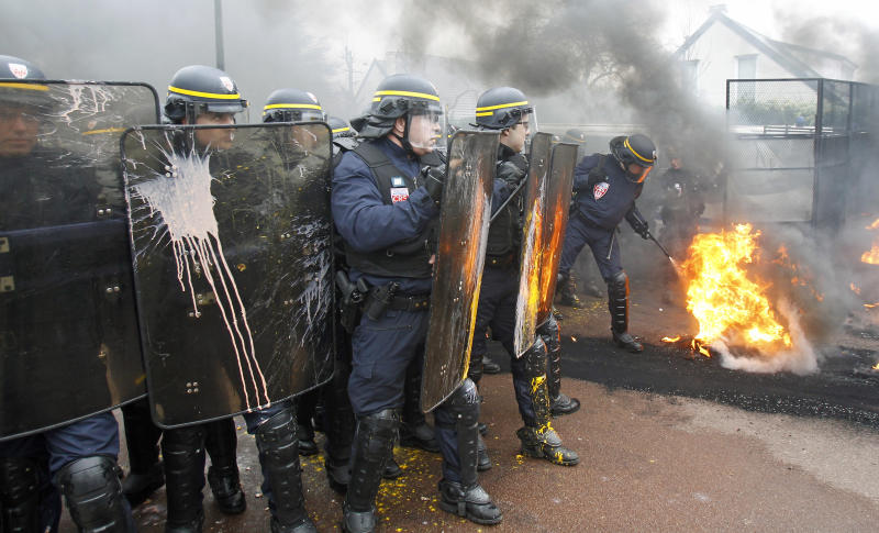FILE - In this March 7, 2013 file photo, a riot police officer extinguishes burning tires during a demonstration by Goodyear workers against layoffs, at the Goodyear headquarters in Rueil Malmaison, west of Paris. With its long vacations, short hours and myriad workers' rights, France has a reputation for being a hard place to do business. Now add this to the mix: A law working its way through parliament would grant amnesty to workers who have ransacked their company's offices or threatened their bosses in the midst of labor disputes. (AP Photo/Remy de la Mauviniere, File)