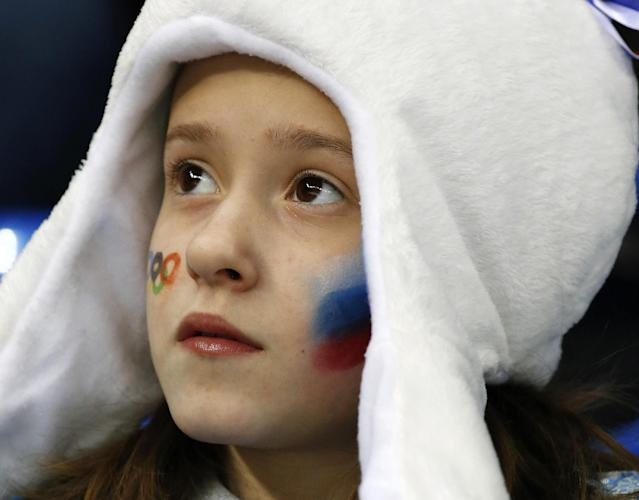 A young Russian hockey fans watches the women's game between Russia and Germany at Shayba Arena during the 2014 Winter Olympics, Sunday, Feb. 9, 2014, in Sochi, Russia. (AP Photo/Julio Cortez)