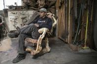 Tim Duncan sits in the redwood burl rocking chair he crafted at his shop in Orick, California June 3, 2014. Duncan sells most of his rustic furniture and carvings outside of the small Northern California town. Picture taken June 3, 2014. REUTERS/Nick Adams (UNITED STATES - Tags: BUSINESS)
