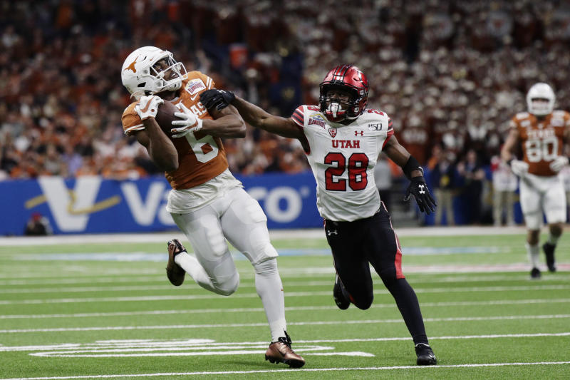 Texas wide receiver Devin Duvernay (6) makes a catch next to Utah defensive back Javelin Guidry (28) during the first half of the Alamo Bowl NCAA college football game in San Antonio, Tuesday, Dec. 31, 2019. (AP Photo/Eric Gay)