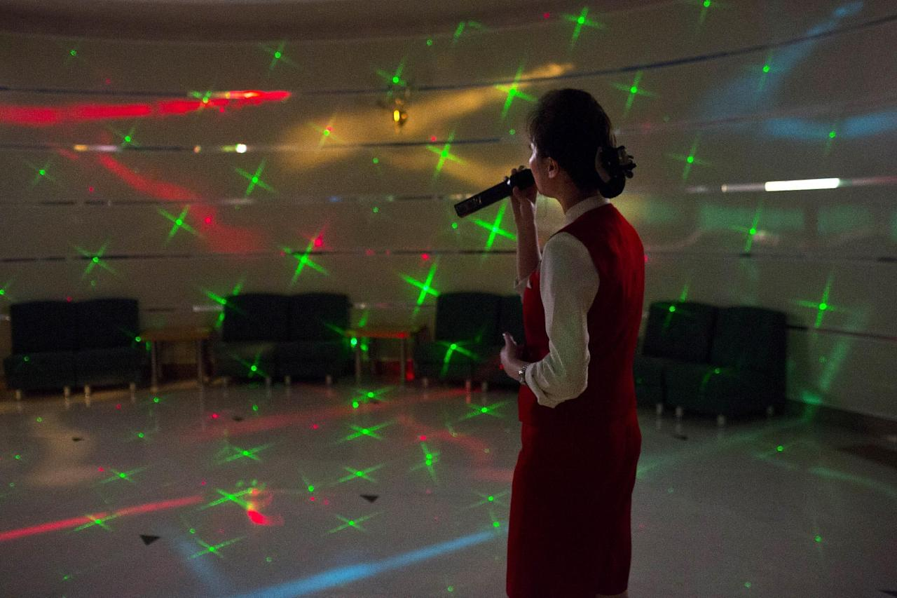 A North Korean woman sings karaoke at the Hyangsan Hotel at the foot of Mount Myohyang, North Korea, Saturday, Feb. 23, 2013. (AP Photo/David Guttenfelder)