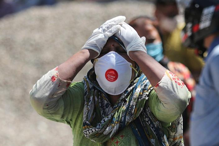 A relative of a person who died of COVID-19 reacts at a crematorium in Jammu, India, on April 25, 2021.