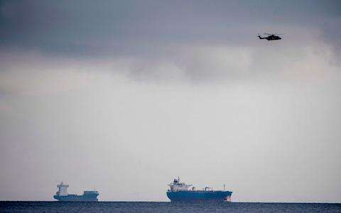 A helicopter flies over the sea off of Copenhagen Harbour where the world's largest privately-built submarine sank - Credit: Bax Lindhart/AFP