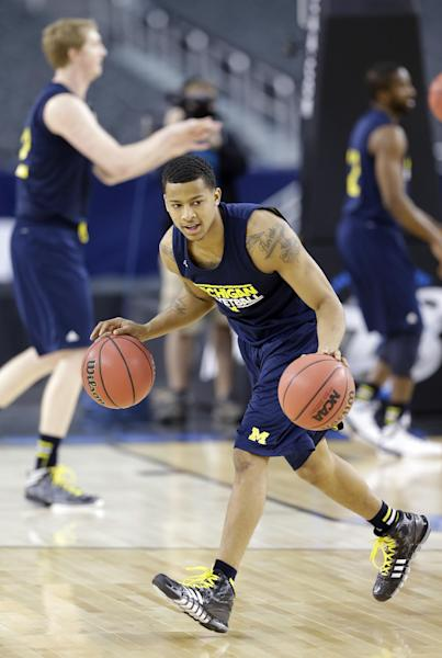 CORRECTS CITY TO ARLINGTON, TEXAS; NOT DALLAS - Michigan's Trey Burke dribbles two balls during practice for a regional semifinal game in the NCAA college basketball tournament, Thursday, March 28, 2013, in Arlington, Texas. Michigan faces Kansas on Friday. (AP Photo/David J. Phillip)