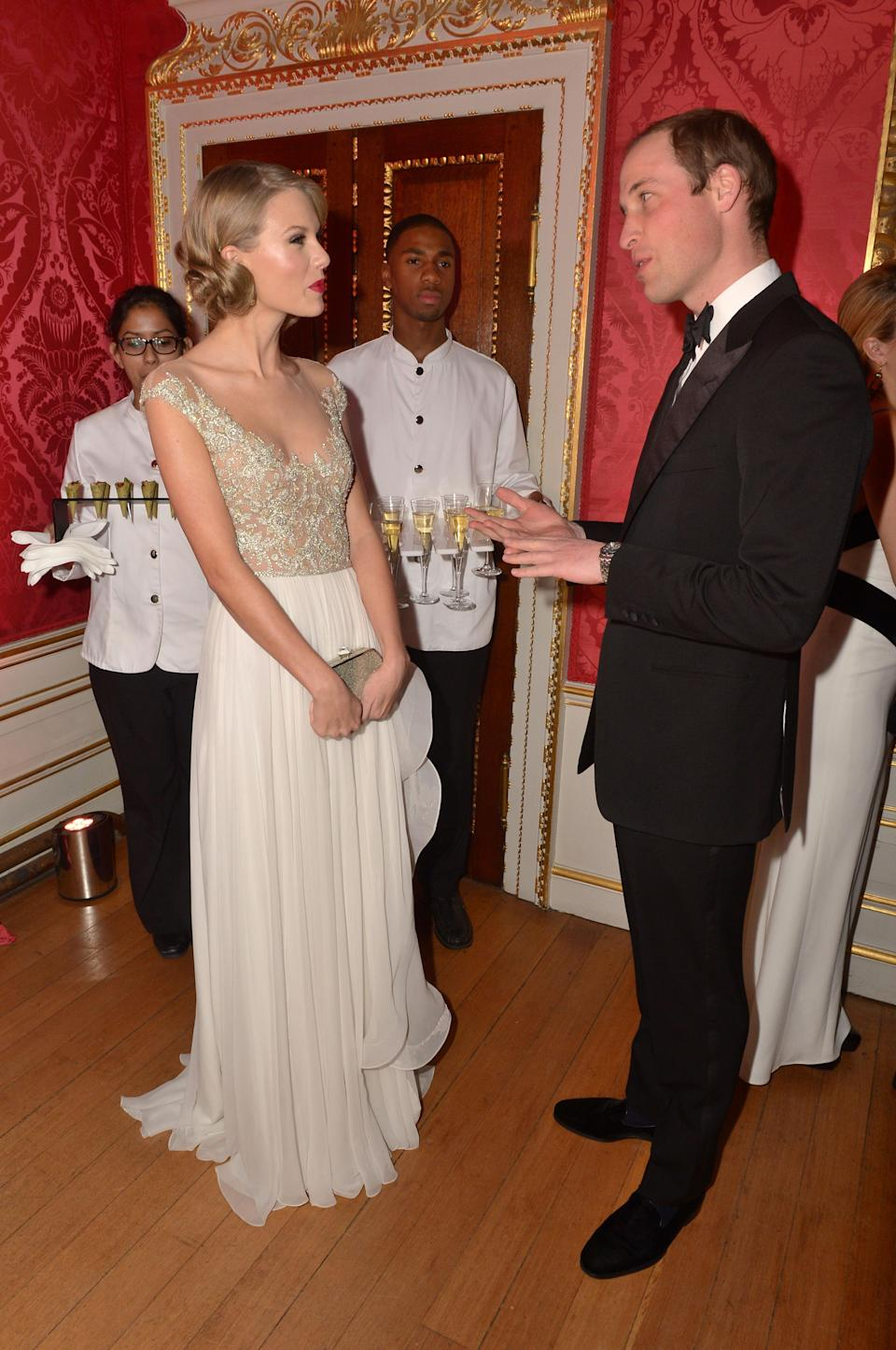 <p>In one of the most famous pop duets of all time, Prince William joined Taylor Swift on stage for a surprise rendition of 'Living on a Prayer' back in 2013. The singer chose a sweeping gown for the charity event finished with a regal bun and red lip. <em>[Photo: Getty]</em> </p>