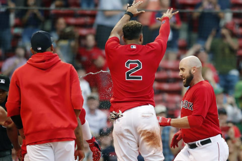 Boston Red Sox's Xander Bogaerts (2) celebrates as Travis Shaw, right, crosses home plate on his walkoff grand slam during the 11th inning of a baseball game against the Texas Rangers, Monday, Aug. 23, 2021, in Boston. (AP Photo/Michael Dwyer)
