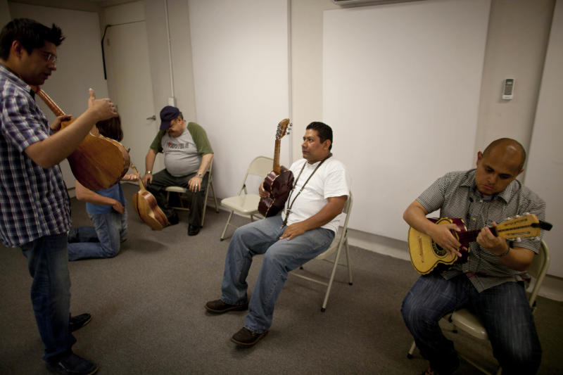 In this Oct. 22, 2012 photo, students attend a class at the Mariachi School Ollin Yoliztli in Mexico City. The new mariachi school in Mexico City is seeking to revive a music that's lost ground over the years. The school, whose name means life and movement in indigenous Nahautl, teaches folk bands how to play professionally while grooming a new generation of songwriters and composers. (AP Photo/Alexandre Meneghini)