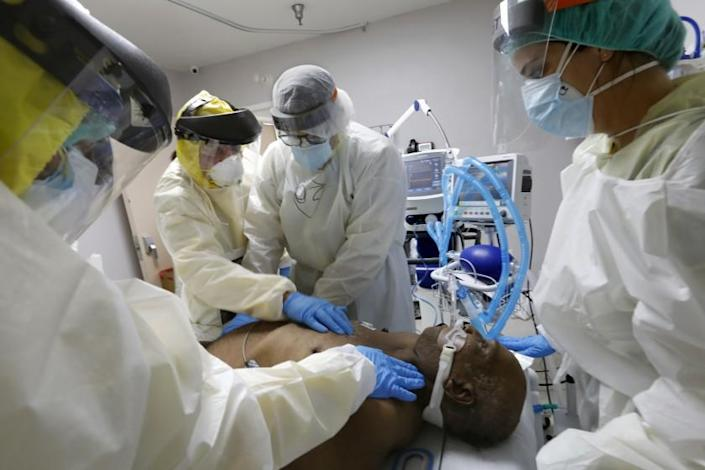 HOUSTON, TEXAS-JULY 1, 2020-Medical Student Osvaldo Perez, 40, (center) and Leyanet Gonzalez, 27 (right) attempt to rescucitate COVID-19 patient Terry Hill, 65, as Dr. Jospeh Varon, left, checks for a pulse on Wednesday at Houston's United Memorial Medical Center. At United Memorial Medical Center in Houston, Texas, Dr. Joseph Varon leads a team to fight the increasing number of coronavirus patients in the expanded Covid-19 ward on July 1, 2020. (Carolyn Cole/Los Angeles Times)
