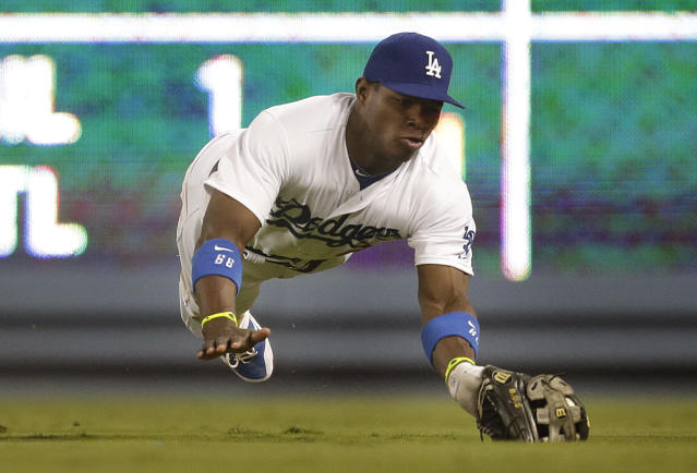 Los Angeles Dodgers' Yasiel Puig catches a ball hit by Arizona Diamondbacks' Chris Owings during the sixth inning of a baseball game on Wednesday, Sept. 11, 2013, in Los Angeles. (AP Photo/Jae C. Hong)
