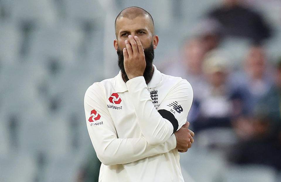 FILE - In this Dec. 2, 2017, file photo, England's Moeen Ali puts his hand over his face after bowling to an Australian batsman during their Ashes test match in Adelaide. Team allrounder Ali was isolating in Sri Lanka on Monday, Jan. 4, 2021, after testing positive for the coronavirus upon his arrival in the South Asian country for the team's two-test cricket tour. (AP Photo/Rick Rycroft, File)