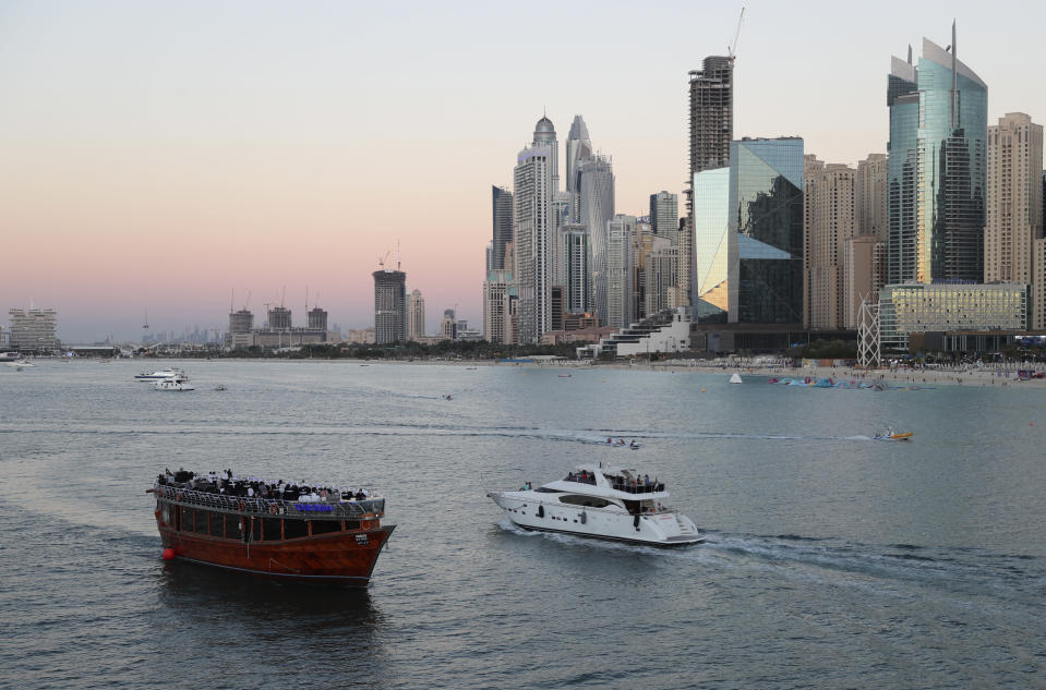 Tourists on a yacht as they pass a traditional dhow serving a dinner cruise, in Dubai, United Arab Emirates, Tuesday, Jan. 12, 2021. With peak tourism season in full swing, coronavirus infections are surging to unprecedented heights, with daily case counts nearly tripling in the past month, forcing Britain to slam shut its travel corridor with Dubai last week. But in the face of a growing economic crisis, the city won't lock down and can't afford to stand still. (AP Photo/Kamran Jebreili)