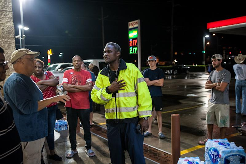A Beaumont police officer attempts to stop people from taking water outside a local convenience store.  (Joseph Rushmore for HuffPost)