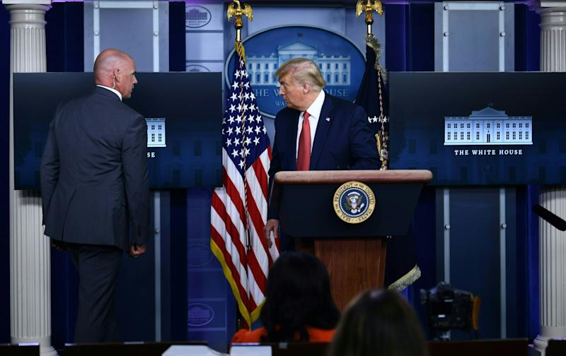 US President Donald Trump is being removed from the Brady Briefing Room of the White House in Washington, DC, on August 10, 2020.