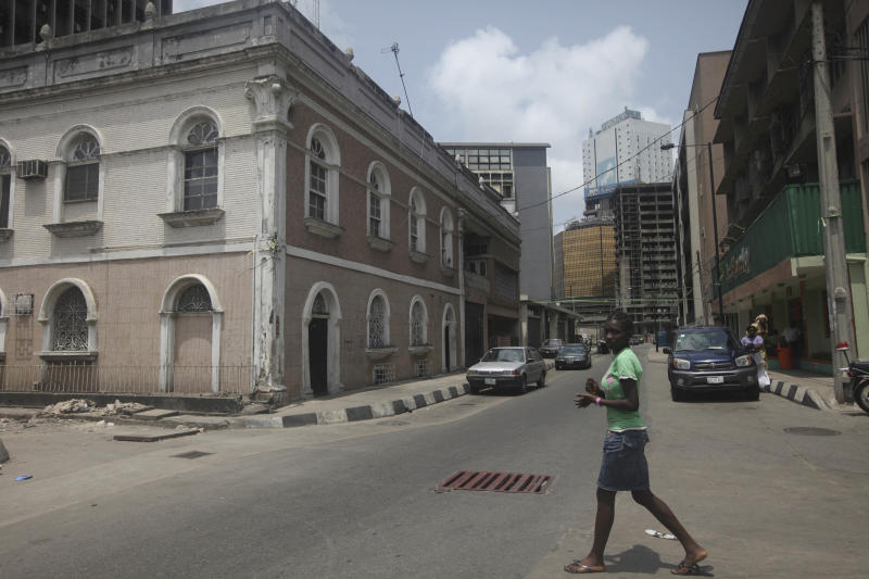 In this photo taken Sunday, April. 1, 2012, a girl walks past the Water house, left, built in 1895 by Candido Da Rocha which is one of the oldest and best kept examples of Brazilian houses on the island in Lagos, Nigeria. What is predicted to become the most populous city in Africa was initially ignored by the Portuguese explorers who first dominated it, served as a hub for a brutal slave trade and once held the hope of a continent that even now struggles to overcome its colonial past.(AP Photos/Sunday Alamba)