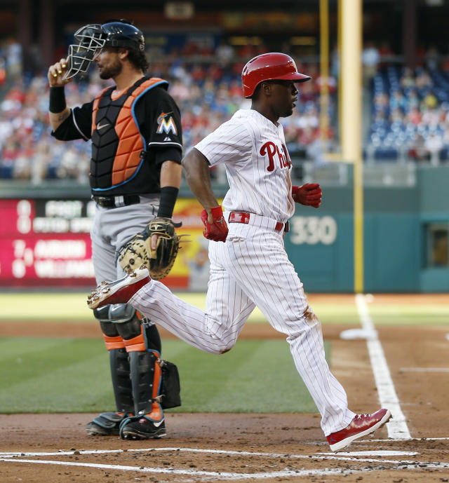 Philadelphia Phillies' Jimmy Rollins, right, scores past Miami Marlins catcher Jarrod Saltalamacchia after stealing third base and then scoring on a throwing error by Saltalamacchia during the first inning of a baseball game, Tuesday, June 24, 2014, in Philadelphia. (AP Photo/Matt Slocum)
