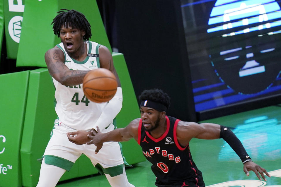 Boston Celtics center Robert Williams III (44) passes the ball while pressured by Toronto Raptors guard Terence Davis (0) during the first half of an NBA basketball game, Thursday, March 4, 2021, in Boston. (AP Photo/Charles Krupa)
