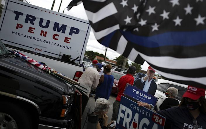 President Donald Trump hold signs during a rally outside an early voting polling location - Bloomberg