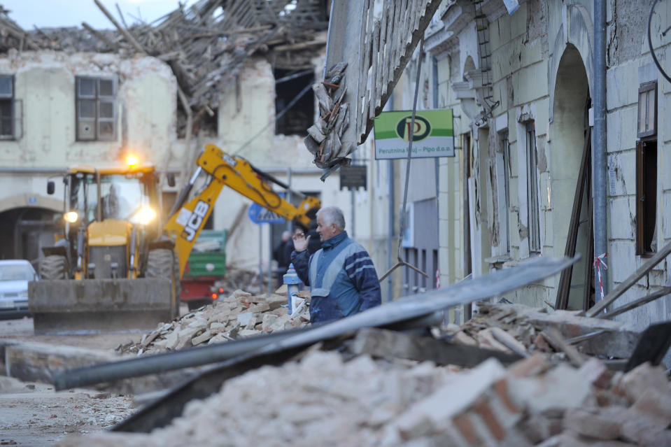 A man stands amidst the rubble from buildings damaged in an earthquake in Petrinja, Croatia, Tuesday, Dec. 29, 2020. A strong earthquake has hit central Croatia and caused major damage and at least one death and some 20 injuries in the town southeast of the capital Zagreb. (AP Photo)