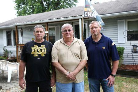 Bruce Reynolds (C) with sons Robert (L) and Bruce Jr., who were once all employed by the now shuttered BorgWarner factory, stand in front of Bruce Reynolds Senior's home in Muncie Indiana, U.S., August 13, 2016. REUTERS/Chris Bergin