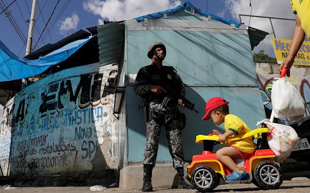 <p>A boy on a cart is pushed near a Brazilian Public-Safety National Force policeman as he patrols an entrance of Chapadao slums complex during a security operation on an effort to crack down on crime in Rio de Janeiro, Brazil, May 15, 2017. (Photo: Ricardo Moraes/Reuters) </p>