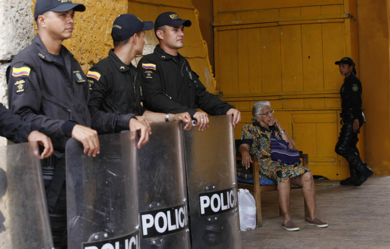 An elderly woman sits as police officers stand guard in Cartagena, Colombia, Thursday, April 12, 2012. Leaders of the western hemisphere will attend the 6th Summit of the Americas in Cartagena on April 14 and April 15. (AP Photo/Dolores Ochoa)