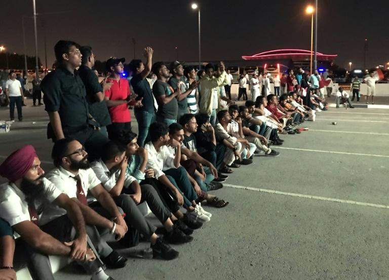 Indian fans who could not get tickets watch on a giant screen outside the stadium where Qatar play India in a World Cup tie