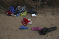 Personal items belonging to migrants lie discarded on the ground after they were smuggled to U.S. soil near the banks of the Rio Grande river in Roma, Texas Saturday, March 27, 2021. Roma, a town of 10,000 people with historic buildings and boarded-up storefronts in Texas' Rio Grande Valley, is the latest epicenter of illegal crossings, where growing numbers of families and children are entering the United States to seek asylum. (AP Photo/Dario Lopez-Mills)