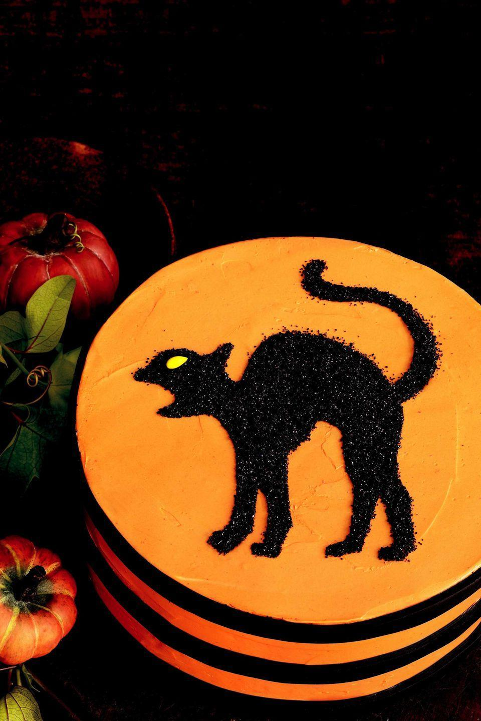 """<p>Even the most superstitious guest will enjoy crossing paths with this black cat, crafted from sparkling sugar.</p><p><strong>To assemble</strong> the stenciled layer cake, fill and frost two 8-inch-round layers with your favorite icing, leaving a smooth surface. Roll out black fondant, into a 1/8-inch-thick sheet, and with a ruler as a guide, cut three strips long enough to wrap around the cake's circumference; adhere, using extra dabs of icing, if needed.</p><p><strong>Re-create this black cat</strong> silhouette by downloading our super-simple stencil. Chill the cake, then immediately before serving, center the stencil on top. Fill in the stencil with black sanding sugar, leaving the edges a little messy for a spooky effect. Add a candy-coated sunflower seed (find a variety at <a href=""""http://www.sunflowerfoodcompany.com/"""" rel=""""nofollow noopener"""" target=""""_blank"""" data-ylk=""""slk:sunflowerfoodcompany.com"""" class=""""link rapid-noclick-resp"""">sunflowerfoodcompany.com</a>) or half a yellow M&M for the cat's eye.</p><p><b><a href=""""https://www.countryliving.com/diy-crafts/a2431/scary-cat-stencil-1008/"""" rel=""""nofollow noopener"""" target=""""_blank"""" data-ylk=""""slk:Get black cat stencil"""" class=""""link rapid-noclick-resp"""">Get black cat stencil</a>.</b> </p>"""