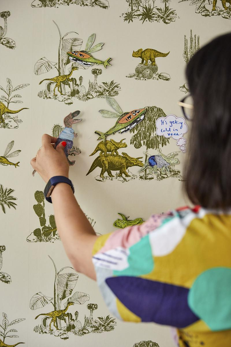 Sian Zeng standing in front of a wall decorated with green and yellow print wallpaper, holding a dinosaur figure up to the wall