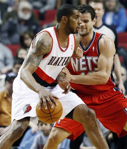 New Jersey Nets' Kris Humphries, right, defends against Portland Trail Blazers' LaMarcus Aldridge, left, in the first quarter of an NBA basketball game, Wednesday, April 4, 2012, in Portland, Ore. (AP Photo/Rick Bowmer)