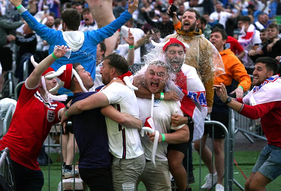 Fans in Manchester celebrate an England goal (PA Wire)