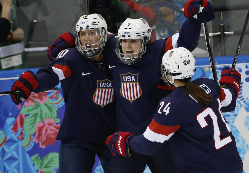 Meghan Duggan, Monique Lamoureux and Josephine Pucci of the Untied States (L-R) celebrate Lamoureux's goal against Switzerland during the 2014 Winter Olympics women's ice hockey game at Shayba Arena, Monday, Feb. 10, 2014, in Sochi, Russia. USA defeated Switzerland 9-0. (AP Photo/Petr David Josek)