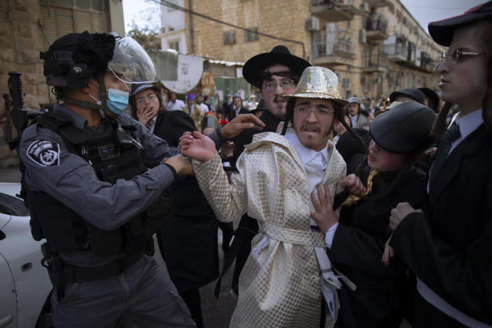 Ultra-Orthodox Jews some wearing costumes scuffle with police officers during celebrations of the Jewish holiday of Purim, in the Mea Shearim ultra-Orthodox neighborhood of Jerusalem, Sunday, Feb. 28, 2021. The Jewish holiday of Purim commemorates the Jews' salvation from genocide in ancient Persia, as recounted in the biblical Book of Esther. (AP Photo/Oded Balilty)