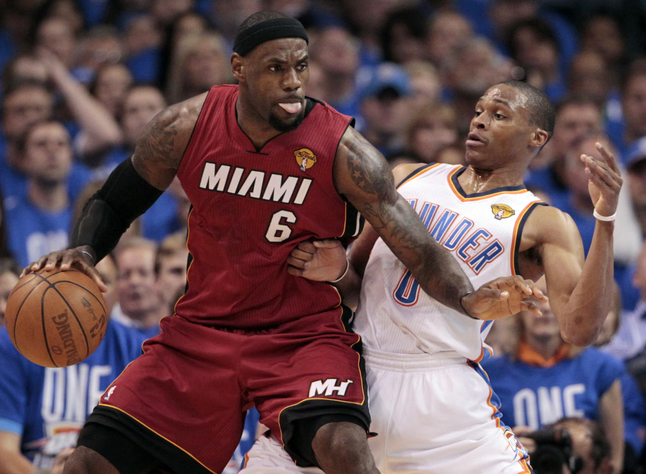 Miami Heat small forward LeBron James moves with the ball as Oklahoma City Thunder point guard Russell Westbrook (0) defends during the first half at Game 1 of the NBA finals basketball series, Tuesday, June 12, 2012, in Oklahoma City. (AP Photo/Jeff Roberson)