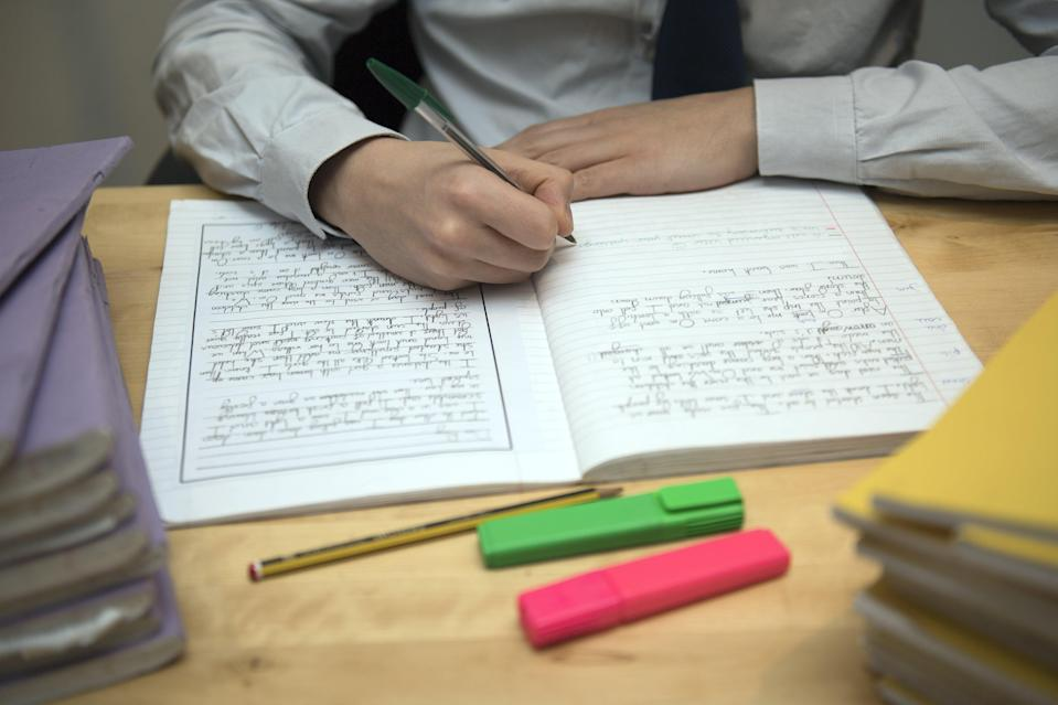 A primary school teacher marking a pupil's English homework (PA) (PA Wire)