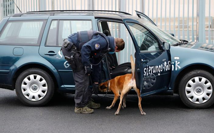 Police with a sniffer dog searches a car which crashed into the main gate of the chancellery in Berlin - FABRIZIO BENSCH /REUTERS