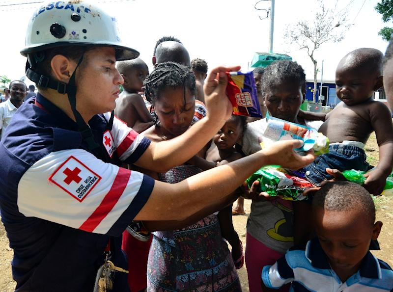 The Costa Rican Red Cross distributes food to migrants at the encampment in Penas Blancas (AFP Photo/Ezequiel Becerra)