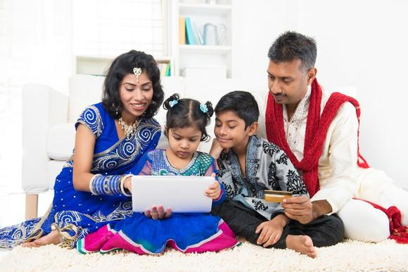 Indian family gathered around laptop making an online purchase.