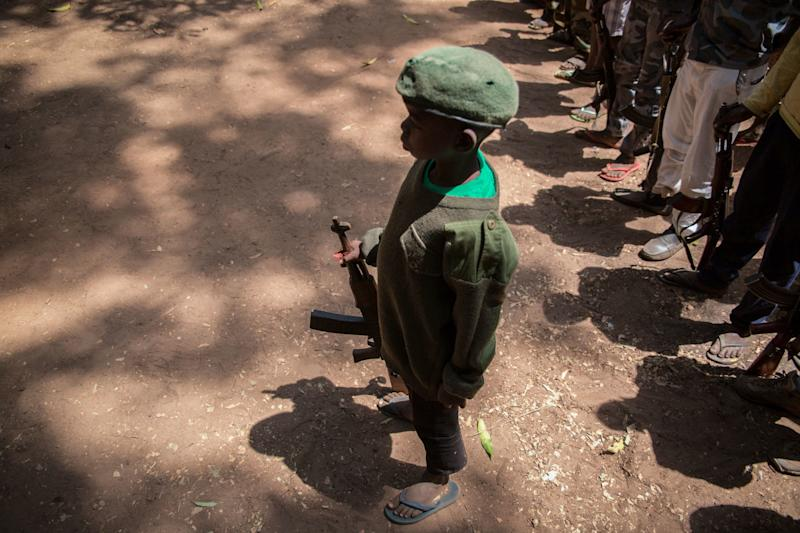 A newly-released child soldier stands with his rifle during a ceremony on Feb. 7, 2018. (STEFANIE GLINSKI via Getty Images)