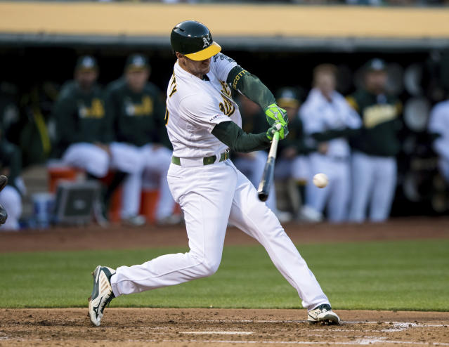 Oakland Athletics Stephen Piscotty hits a two-run double against the Los Angeles Angels in the third inning of a baseball game, Saturday, March 30, 2019 in Oakland, Calif. (AP Photo/John Hefti)