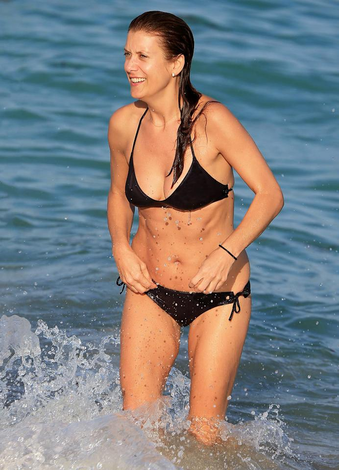"Kate Walsh has been doing some ""Private Practice"" – in the gym! The 45-year-old actress, who also attended the Art Basel festivities, showed off her toned frame as she emerged from the surf in a black string bikini. Earlier this year, the actress stripped down to her birthday suit to appear on the cover of <em>Shape</em>. She also revealed that although she has tried juice cleanses, the cabbage soup diet, and Atkins, what works for her is a portion-controlled diet. ""I'd rather have a smaller serving of something amazing than a plateful of diet food,"" Walsh noted. (12/11/2012)"