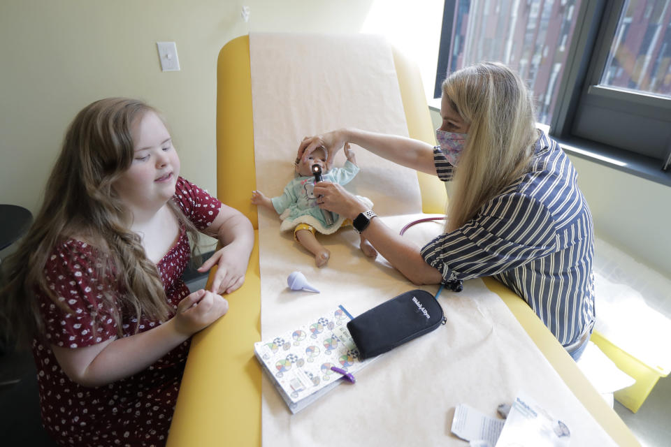 Emilyanne Wade, 12, left, looks on as Tricia Nora, a pediatric nurse practitioner, examines Sophia, Wade's baby doll, Wednesday, June 17, 2020, in a medical clinic at Mary's Place, a family homeless shelter located inside an Amazon corporate building on the tech giant's Seattle campus. The facility is home to the Popsicle Place shelter program, an initiative to address the needs of homeless children with life-threatening health conditions. (AP Photo/Ted S. Warren)